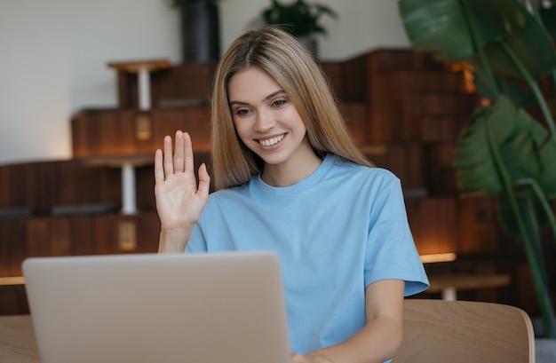 Mulher usando laptop, fazendo videochamada, trabalhando em casa. comunicação do influenciador com assinantes, transmissão ao vivo