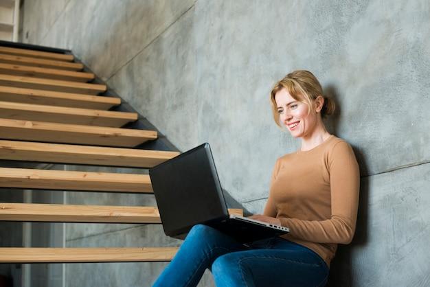 Mulher, usando, laptop, ligado, escadas