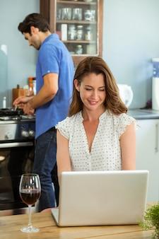 Mulher usando laptop na cozinha