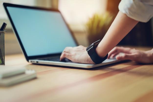 Mulher usando laptop na mesa na sala do escritório.