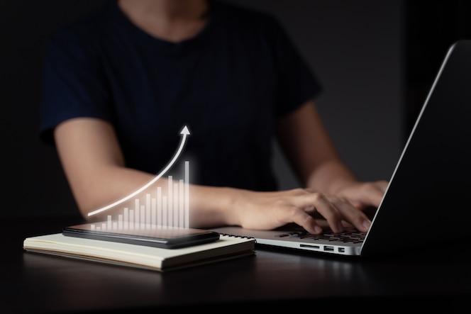 Mulher usando laptop planejando marketing digital com efeito de holograma gráfico