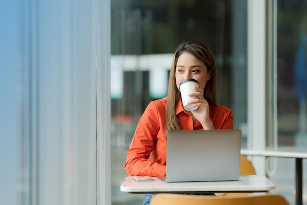 Mulher usando laptop sentada em uma cafeteria