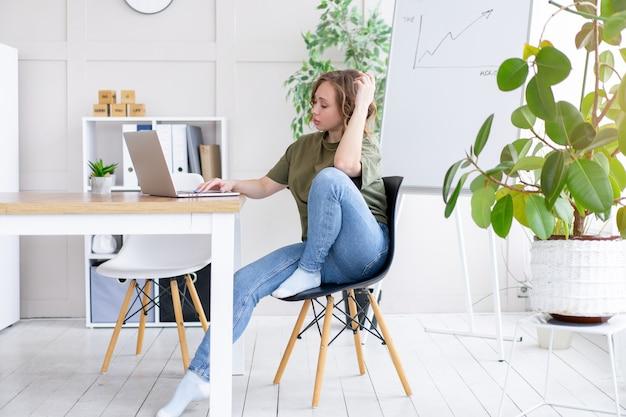 Mulher usando laptop, sentada na mesa, escritório branco interior com planta de casa