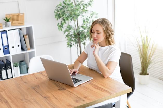 Mulher usando laptop, sentada na mesa, escritório, interior com planta de casa, olhando para a câmera