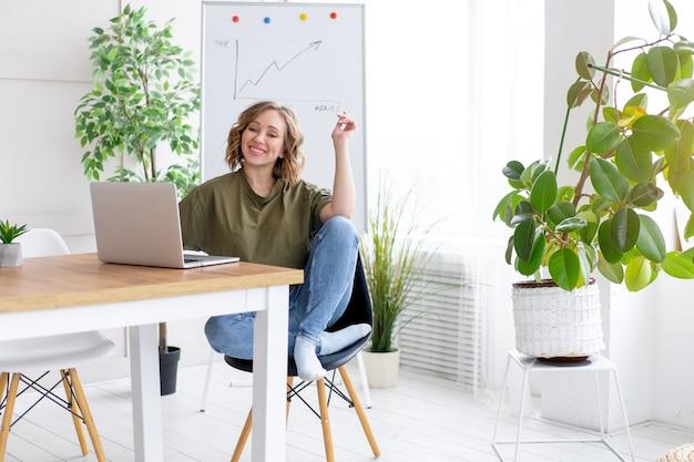 Mulher usando laptop sentado mesa escritório branco interior com planta de casa procurando pessoas de negócios pessoa de negócios online