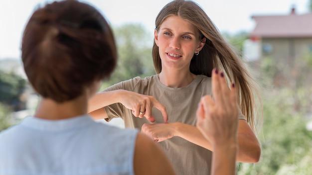 Mulher usando linguagem de sinais ao ar livre para conversar com a amiga