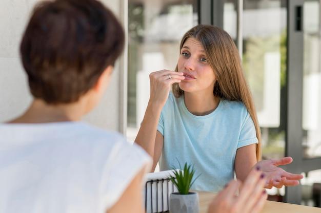 Mulher usando linguagem de sinais para se comunicar com a amiga