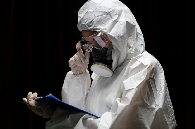 Mulher usando luvas com traje de proteção química de risco biológico e máscara. está escrevendo um relatório em papel.