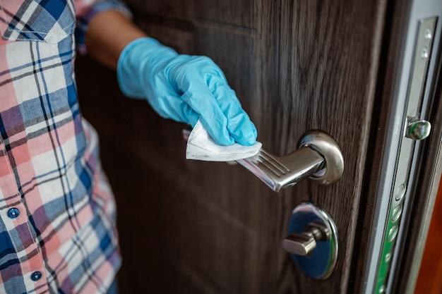 Mulher usando luvas de borracha e desinfetando maçaneta da porta