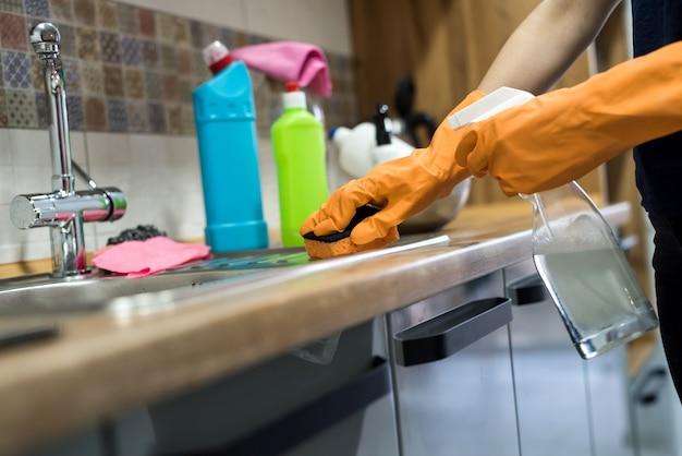 Mulher usando luvas de borracha e limpando os armários ou a superfície da cozinha. conceito de limpeza