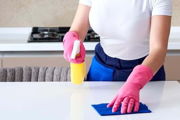 Mulher usando luvas de borracha, limpando a mesa com um pano. desinfetar a mesa da cozinha com água sanitária