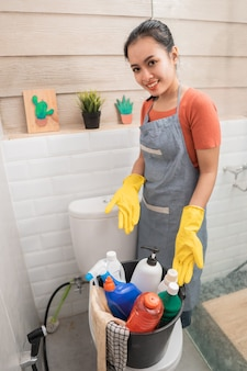 Mulher usando luvas, mostrando ferramentas de limpeza no balde. borrifador de garrafa, garrafa de líquido de limpeza e pano em um balde no banheiro
