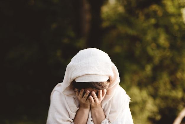 Mulher usando manto bíblico chorando - conceito confessando pecados