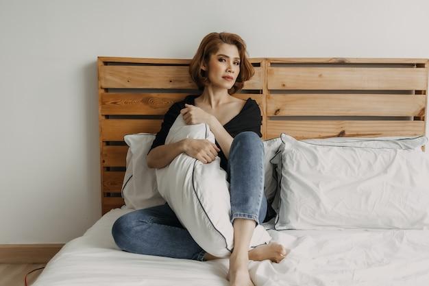 Mulher usando maquiagem completa relaxando na cama conceito de solidão