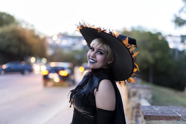 Mulher usando maquiagem de bruxa e fantasia com um chapéu decorado, capturada em uma rua