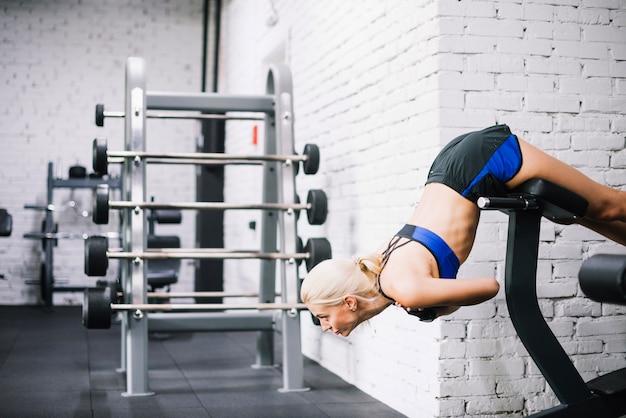 Mulher usando máquina de exercícios para extensões traseiras