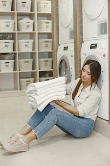 Mulher usando máquina de lavar, lavando a roupa. jovem pronta para lavar roupas. interior, conceito de processo de lavagem