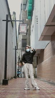 Mulher usando máscara caminhando em um antigo beco