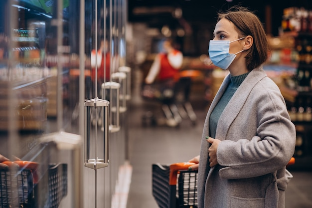 Mulher usando máscara e fazendo compras em um supermercado