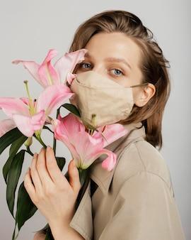 Mulher usando máscara e segurando um buquê de flores