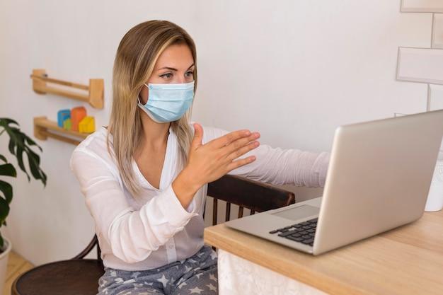 Mulher usando máscara em casa
