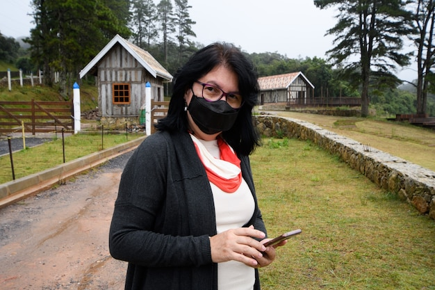Mulher usando máscara em um ambiente rural em um dia de muita neblina e segurando o telefone