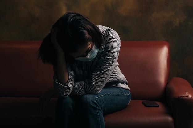 Mulher usando máscara facial com depressão coçando a cabeça enquanto está sentada no sofá. depressão associada a covid-19