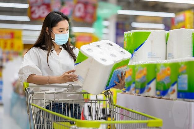 Mulher usando máscara facial comprando no supermercado