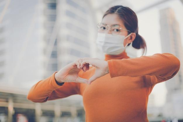 Mulher usando máscara facial e fazendo gestos de coração com as mãos