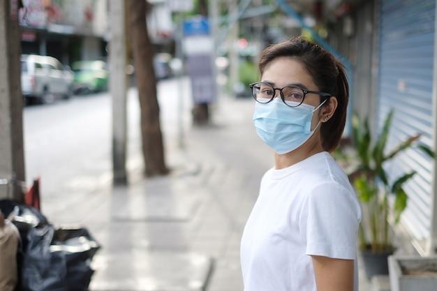 Mulher usando máscara facial médica durante caminhada em calçada de rua e mercado noturno, prevenir o coronavírus ou doença do vírus corona (covid-19). saúde, conceito de vida