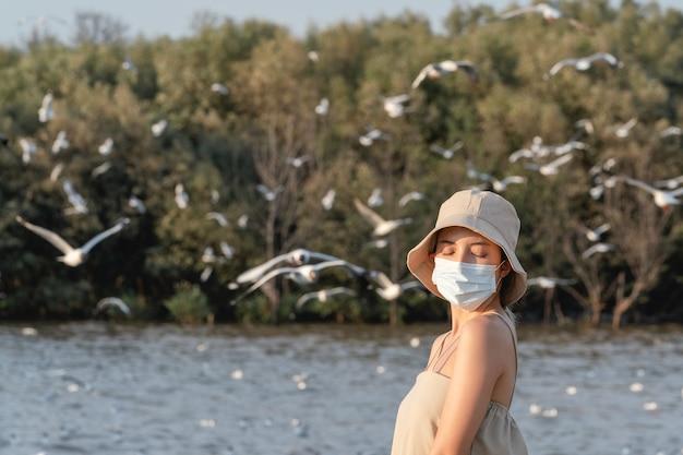 Mulher usando máscara facial olhando para a costa com gaivotas voando no fundo, sentindo-se livre