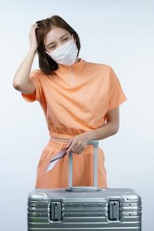 Mulher usando máscara facial, passaporte de bagagem e cartão de embarque, novo conceito normal de viagem. (código de barras falso)