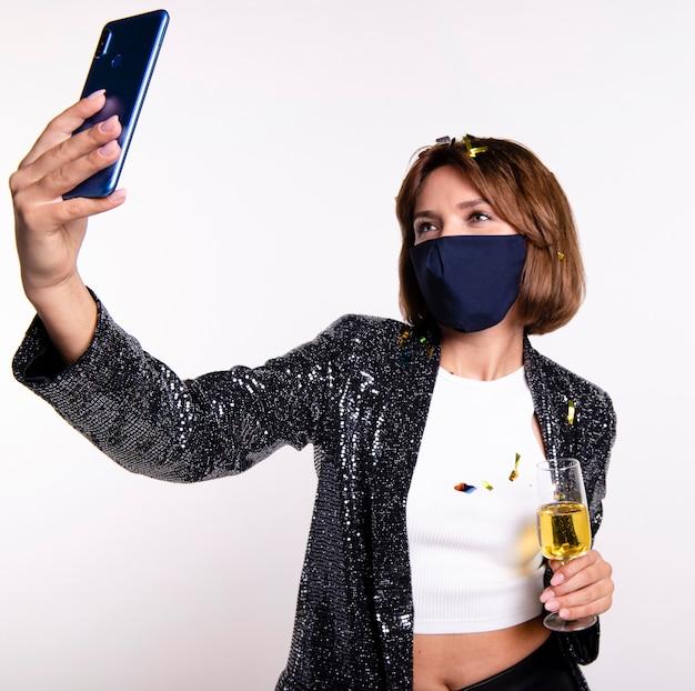 Mulher usando máscara facial tirando uma selfie
