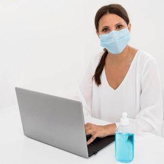 Mulher usando máscara médica ao lado de desinfetante para as mãos