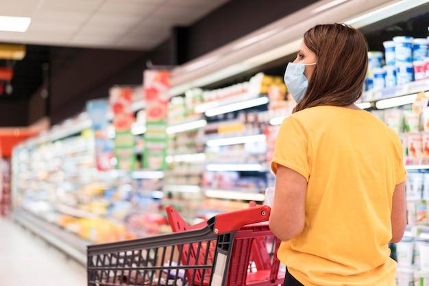 Mulher usando máscara médica comprando produtos