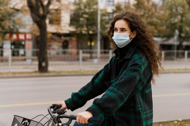 Mulher usando máscara médica e andando de bicicleta