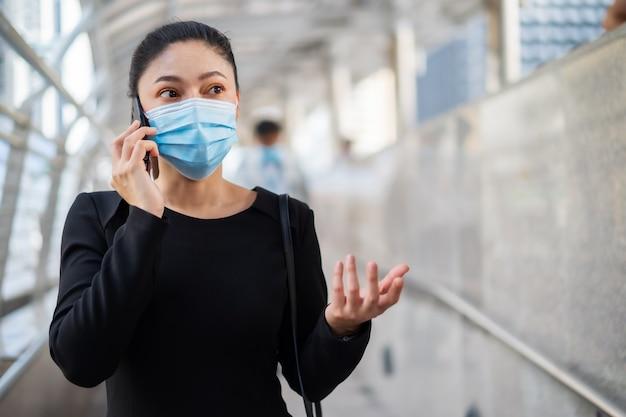 Mulher usando máscara médica e falando no celular