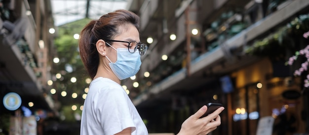 Mulher usando máscara médica e usando smartphone durante uma caminhada no mercado noturno, evita o coronavírus ou doença do vírus corona (covid-19). saúde, conceito de vida