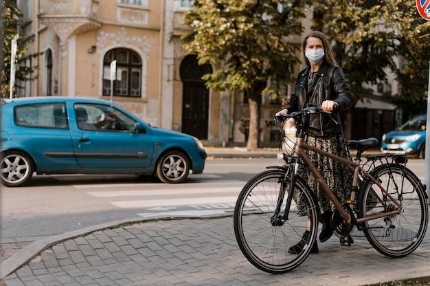 Mulher usando máscara médica e visão de longo prazo de bicicleta