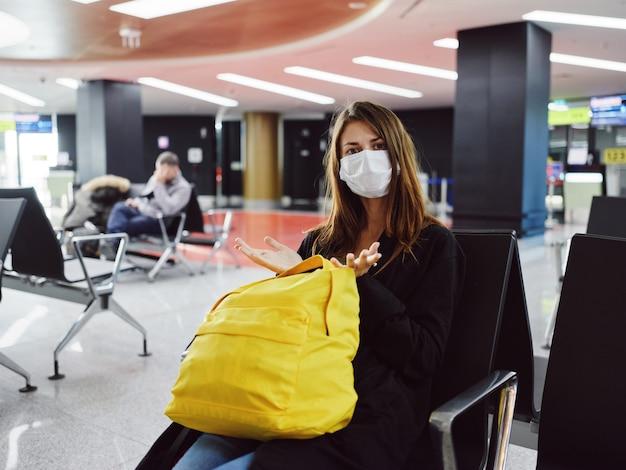 Mulher usando máscara médica, mochila amarela, esperando passageiro do aeroporto
