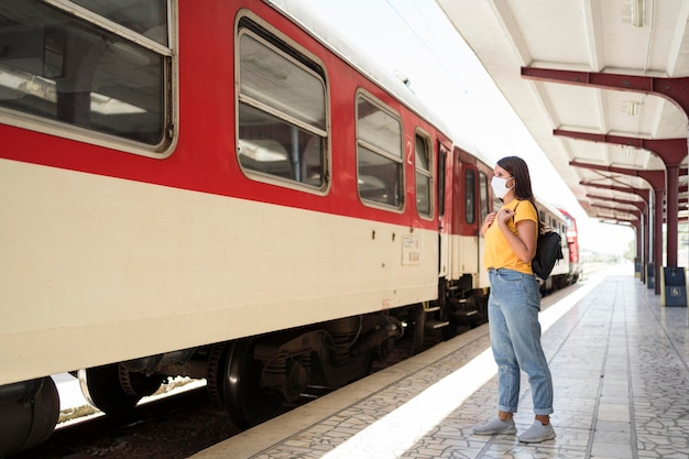 Mulher usando máscara médica pronta para entrar no trem