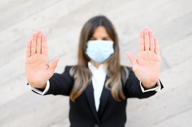 Mulher usando máscara para proteção contra doenças, mostra gesto de parar com as mãos