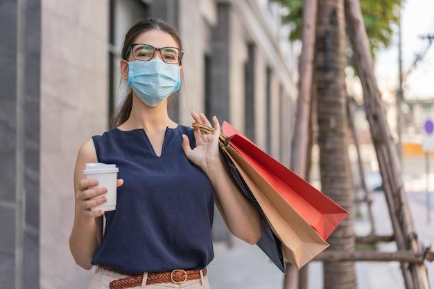 Mulher usando máscara protetora médica segurando uma xícara de café e carregando sacolas de compras anda na rua no shopping center