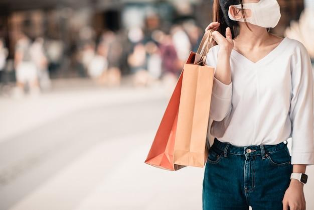 Mulher usando máscara protetora, segurando sacos de papel.