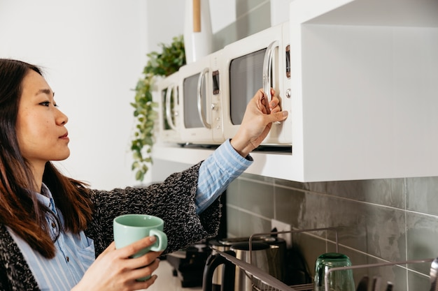 Mulher usando microondas em casa