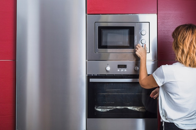 Mulher, usando, modernos, microonda, forno