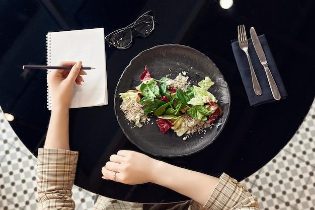 Mulher usando notebook e comer salada fresca, vista superior Foto Premium