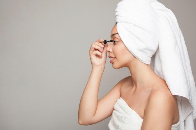 Mulher usando o cílio dos olhos curlers após o banho