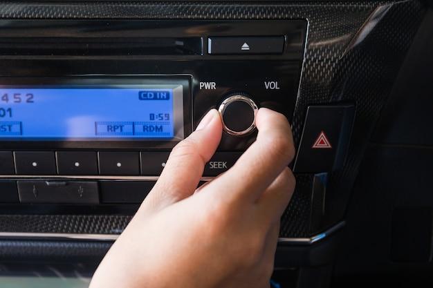 Mulher usando o controle de áudio de volume de carro.