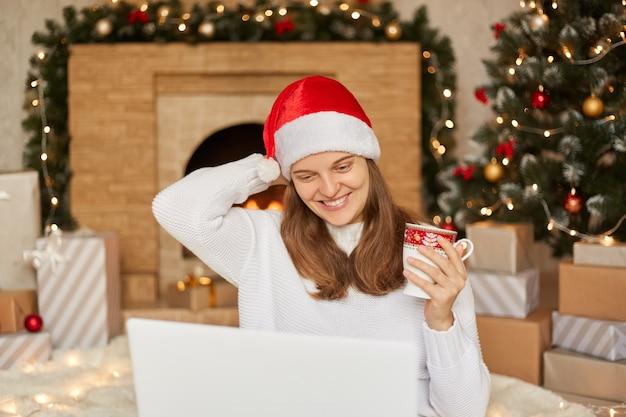 Mulher usando o laptop em casa enquanto está sentado no chão com uma xícara de café ou chá, olha para a tela do computador, tocando a cabeça dela, usando chapéu de papai noel, transmitindo ao vivo, parabenizando seus seguidores.